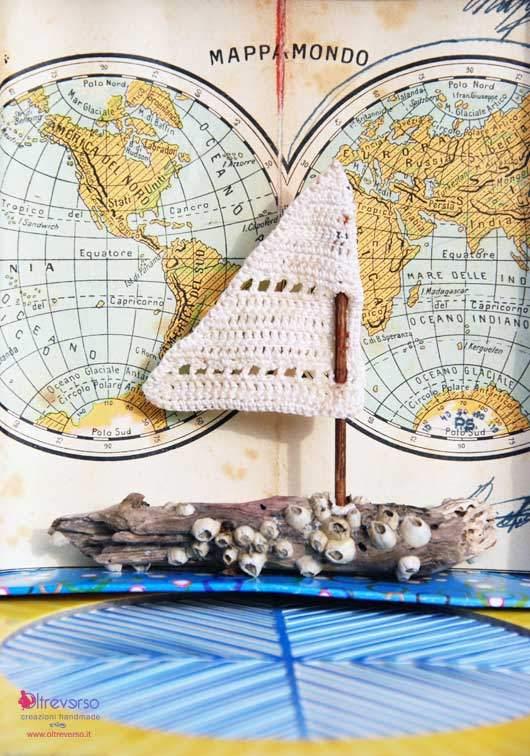 Una barca a vela con i legnetti portati dal mare e la vela all'uncinetto