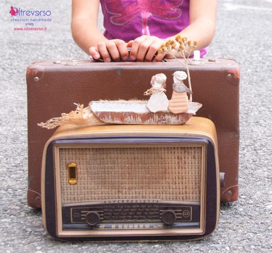 valige e radio vecchia con scultura di sassi