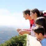 una famiglia in vacanza in montagna davanti a un panorama