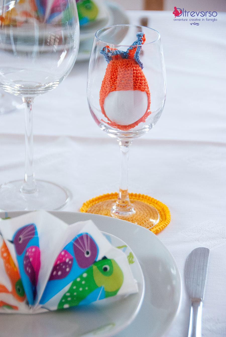 la tavola di pasqua con uova bianche con il cappello all'uncinetto